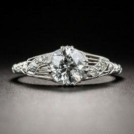 A resplendent original Art Deco finger-hugger, beautifully die-struck and hand-finished in platinum, circa 1920s-30s, presents a gorgeous icy-white European-cut diamond, weighing 1.13 carats. The scintillating stone is elegantly embellished on each side with pierced mirror-image design motifs aglitter with pairs of small round diamonds leading to a decoratively embossed ring shank. Stamped inside ring shank ' Bud & Blossom'. GIA Diamond Grading Report stating: H color - VS1 clarity.