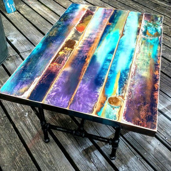 Coffee table painted in jewel tones on reclaimed wood from vintage door. Modern abstract art with trendy boho colors. Industrial pipe leg