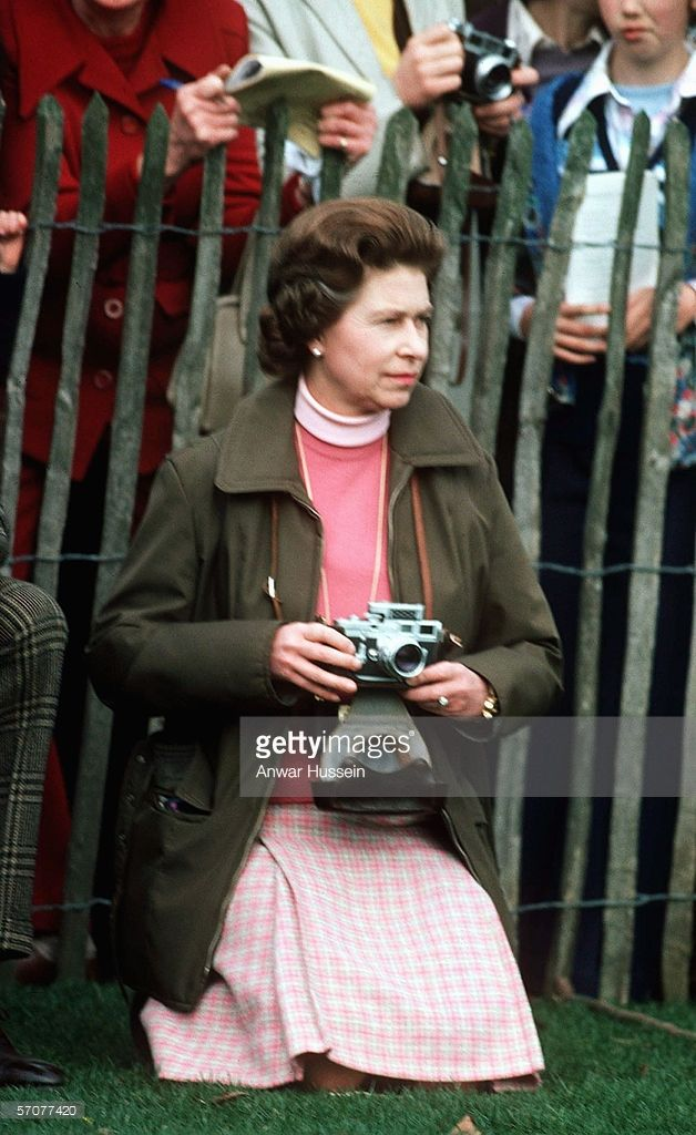Queen Elizabeth II kneels down with a camera and watches the Badminton Horse Trials on October 14, 1975 in Badminton, England.
