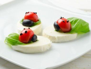 Für Marienkäfer Caprese zunächst den Mozzarella abtropfen lassen und in nicht zu dünne Scheiben schneiden. Auf der Seite des Strunks die