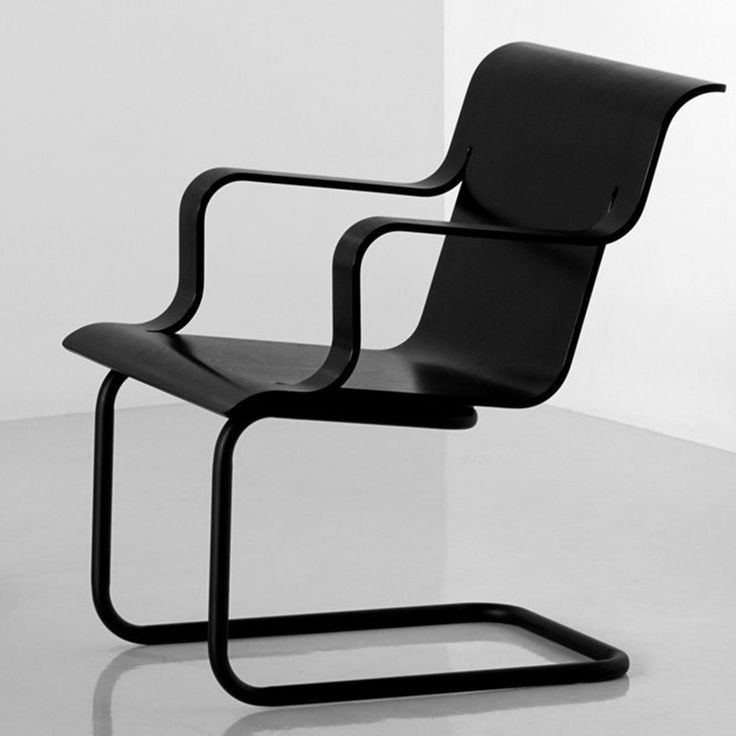 """Artek Armchair 26 The Armchair 26 by Artek features a seat with black painted finish over a simple cantilevered painted steel tube frame. The Artek Armchair 26 was designed by Alvar Aalto: """"The Armchair 26 achieves its bold character from seat and arms shaped of a single piece of pressed birch plywood."""""""