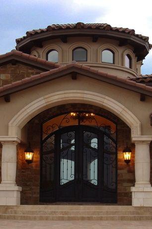 Mediterranean Front Door with Transom window, picture window, Exterior brick, Arched window, exterior stone floors