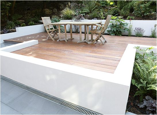 contemporary garden decking area with low rendered white walls - Nina ...