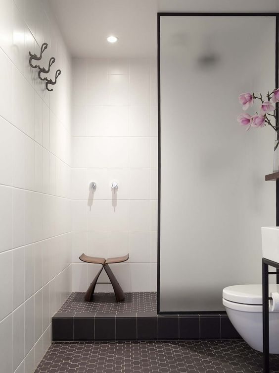 The bathroom - a windowless space in Carroll's small apartment - now features Deco-flavoured floor tiles and a simple shower area. Photograph by David Straight.: