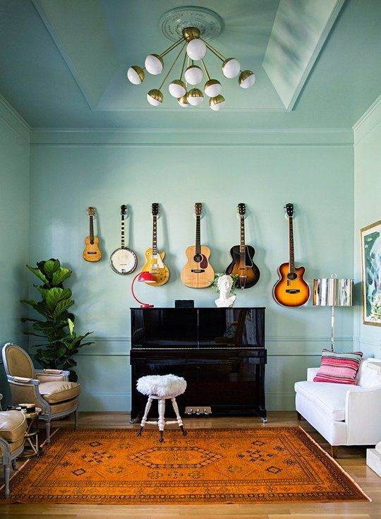 Eclectic living room featuring a black lacquer piano, mint green walls, guitars on display and a printed rug | Domino