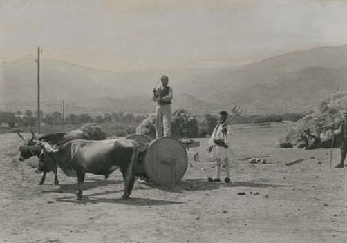 A farmer stands on a wagon pulled by oxen; another holds a pitchfork. 1900s. Location: Olympos, Greece. Photographer: FRED BOISSONNAS/National Geographic Creative