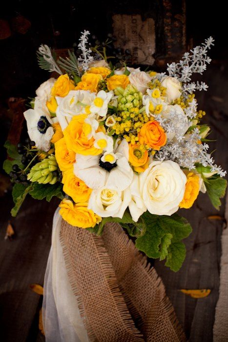 Bridal bouquet of white roses, gold roses, gold ranunculus, yellow hyacinth, grey foliage, paperwhites, mimosa, acacia, scented geranium.