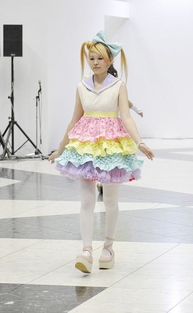 Colorful and frilly handmade dress on the catwalk. Design Festa