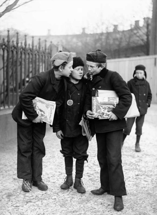 Newspaper boys take a break from work to light a cigarette on Karl Johans gate, Oslo, Norway.  Photo by Anders Beer Wilse, 1905.