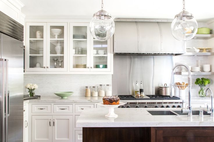 white cabinets, wood island cabinets, globe pendants, arched stainless hood, slab backsplash