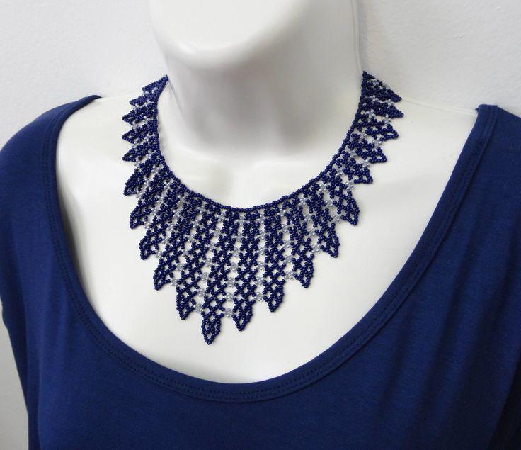 Colar confeccionado com miçangas azul escuro com cinza brilhante. Acabamentos em metal niquelado. <br>Comprimento: 35 cm + 7 cm de corrente extensora <br>Largura no meio do colar ( bico): 8 cm