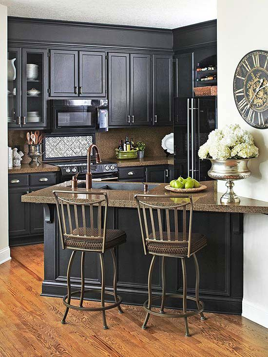 After: Dramatic Makeover...For less than $9,000, the kitchen now sports dramatic painted-black cabinets and granite veneer countertops. Creamy white walls, brushed-nickel cabinet hardware and glossy new appliances add to the kitchen's elegant face-lift.