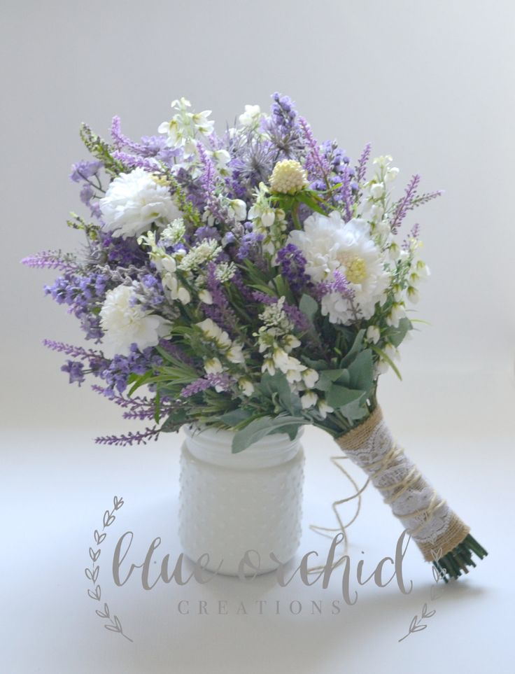 This wildflower bouquet features lavender, purple wildflowers, some white wildflowers, and light blue accents. The shabby chic design has a little bit of a rustic twist with the stems wrapped in burlap, lace, and twine. Makes a gorgeous bridal bouquet. Dimensions: 1 bridal bouquet - about 12 diameter If you need additional items or a different package, please contact me so that I can create a custom listing for you. If you have any questions, you can send me a message! I will respond as…