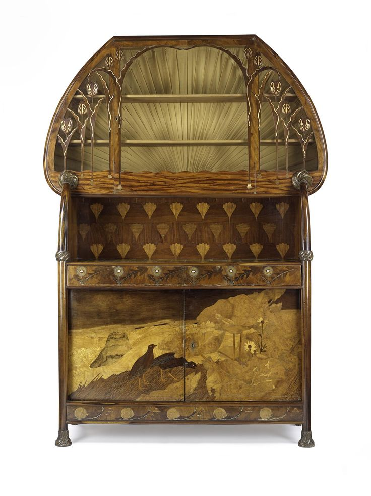 Cabinet, oak carcass, lower section with pictorial marquetry doors inlaid with mother-of-pearl and with metal mounts, upper section with glazed door and silk interior lining: French, Nancy, by Louis Majorelle, 1898.