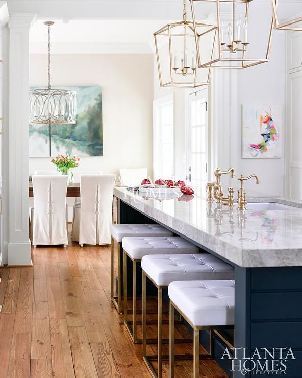 A dark blue wainscoted island, topped with a gray quartzite countertop finished with a sink paired with a vintage brass faucet, seats four Nuevo Chi Counter Stools lit by Darlana Medium Lanterns.