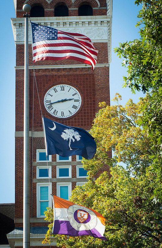 The American, South Carolina and Clemson flags fly in front of the Tillman Hall clock tower on the Clemson University campus, Oct. 29, 2014. (Photo by Ken Scar, Clemson Public Information Officer)