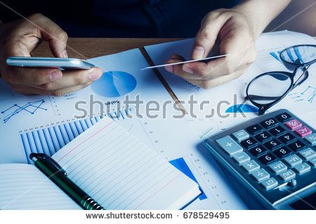 Asian hand man using mobile phone and credit for e commerce online on home office.accessories  document chart notebook eyeglasses pen on wood table background.shopping online.financial.saving concept.