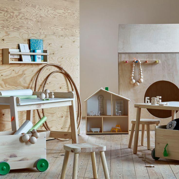 En samling barnmöbler som ett skrivbord, bokhylla, pall, dockhus och låda på hjul.