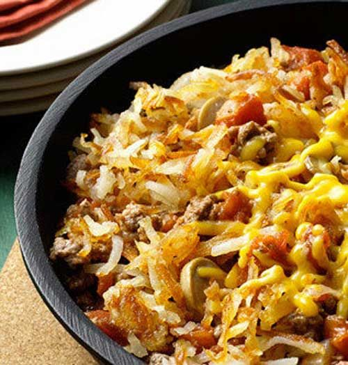 Recipe for Cheesy Hashbrown Skillet Dinner - This 30-minute skillet dinner made with beef, potatoes,cheese, onions and tomatoes is incredibly easy and very satisfying.