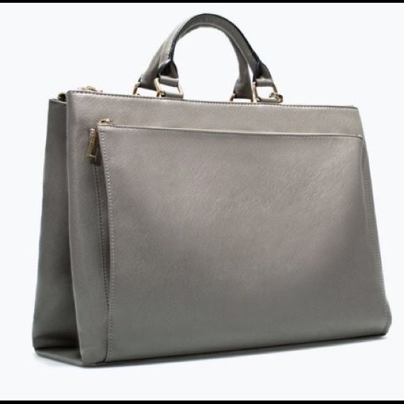 Zara Office City Bag in Grey Saffiano style faux leather city bag by Zara. This bag is perfect for work, school and everything in between. Has two massive zipped compartments that are padded so it's great for all of your electronics and a smaller zipped compartment for pens and cards. Removable cross body strap. Named one of the best work bags in 2014. Sold out online and in stores. The only flaws are some wearing on the bottom of the bag (see 4th pic); otherwise everything else is in…