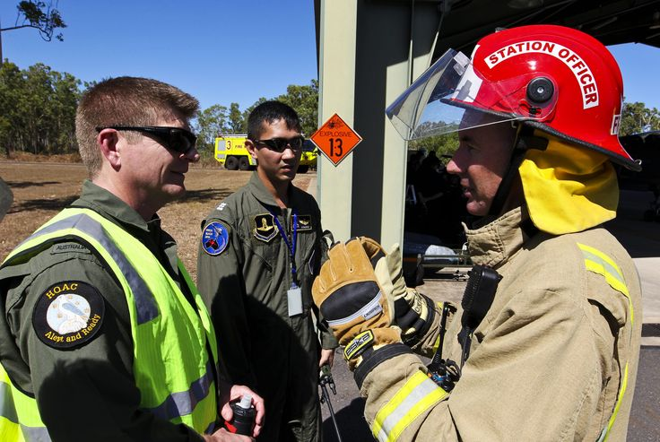 Darwin Airport Aviation Rescue Fire Fighter, Mr Andrew Hendy (right) liaises with RAAF and Royal Thai Air Force personnel during a training exercise.  CPL David Said   Copyright © Commonwealth of Australia, Department of Defence