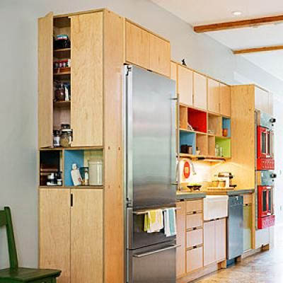 Hartman put caps on each end of the kitchen cabinetry wall to give  more storage. One side is a closed pantry; the other has shelves for cookbooks and vases.