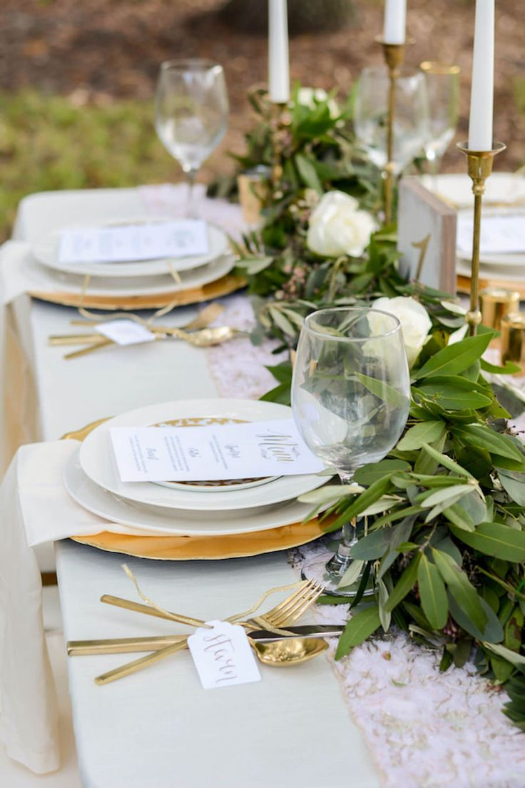 Wedding Reception Tablescape with Lush Greenery Table Runner with Gold Candle Sticks with Gold Chargers with Gold Silverware with Ivory Linens | Andrea Layne Floral Design | Kate Ryan Custom Linens