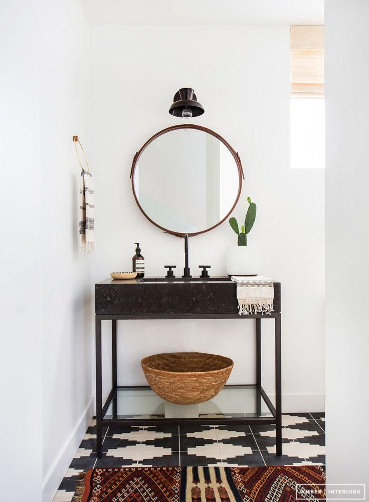 Love this super zen minimalist-meets-boho bathroom with round leather edged mirror and black and white patterned floor tiles.