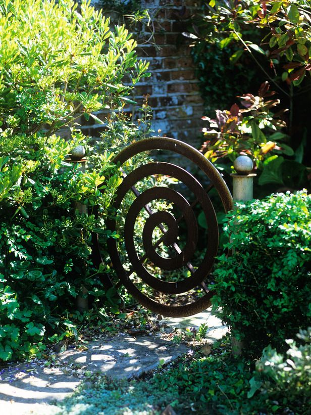 Custom Spiral Gate Draws the Eye - Credit: DK - Garden Design © 2009 Dorling Kindersley Limited Custom Gate -- This spiral metal gate was custom, but there are plenty of lovely designs available ready-made. Set between two sturdy steel posts, it makes a beautiful focal point in a country-style hedge. Regularly trim the foliage away from the hinges & the catch.