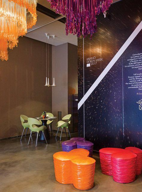 Interior del hotel Nhow Milano con lámparas Nafir en forma de trompeta, bancos tubulares en naranja, fucsia y violeta, y paredes pintadas de color marrón.