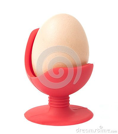 A large organic chicken egg sitting upright in a red armchair style silicone egg cup isolated against white.