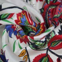 Bílé hedvábí s barevným vzorem ornamentů.