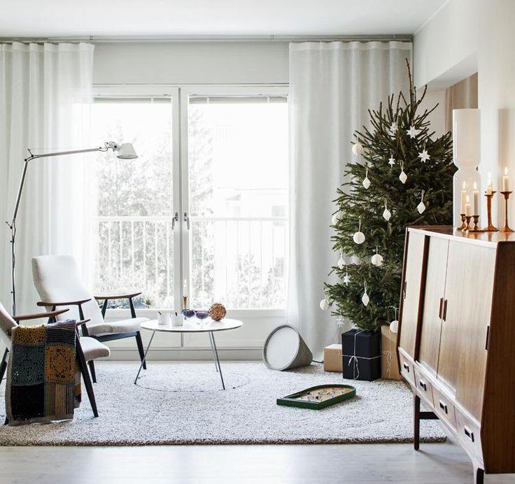 Kuusi on perinteisellä paikallaan olohuoneessa. Olohuoneen nurkassa on Tolomeo-jalkavalaisin ja lattialla betoninen Sektori-valaisin. Kehä-sohvapöytä on Matti Syrjälän suunnittelema. Lappalaisen nojatuolit on ostettu huutokaupasta    HILLITTYÄ JUHLAA   Koti ja keittiö