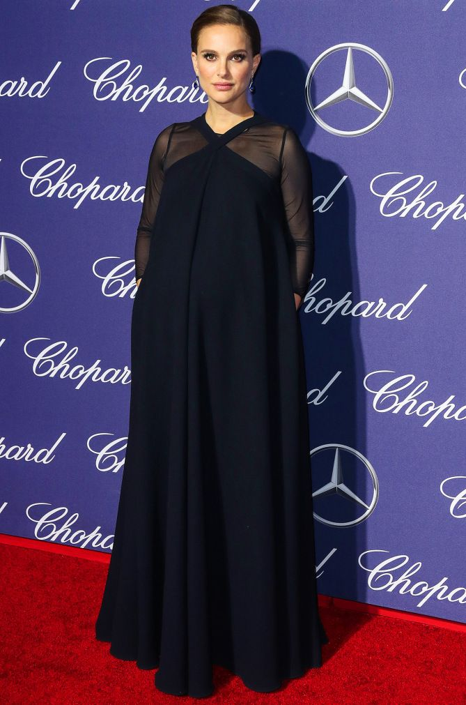Natalie Portman wears a flowing navy Dior wool crepe dress with sheer sleeves and Tiffany & Co. drop earrings to the Palm Springs International Film Festival Awards Gala.