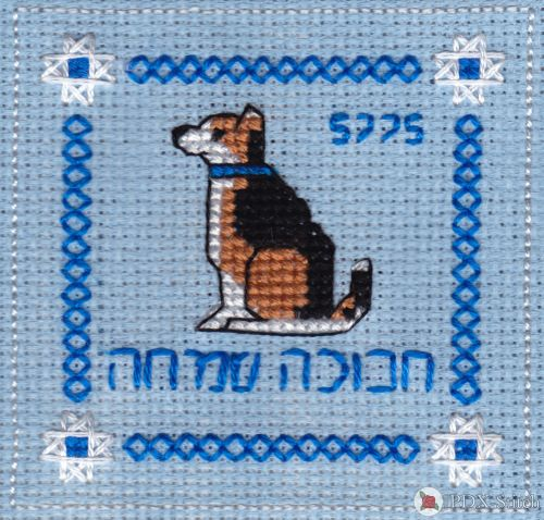 "photograph of a cross stitch square with words '5775' and ""happy hanukkah"" in Hebrew surrounding a dog with a blue collar"