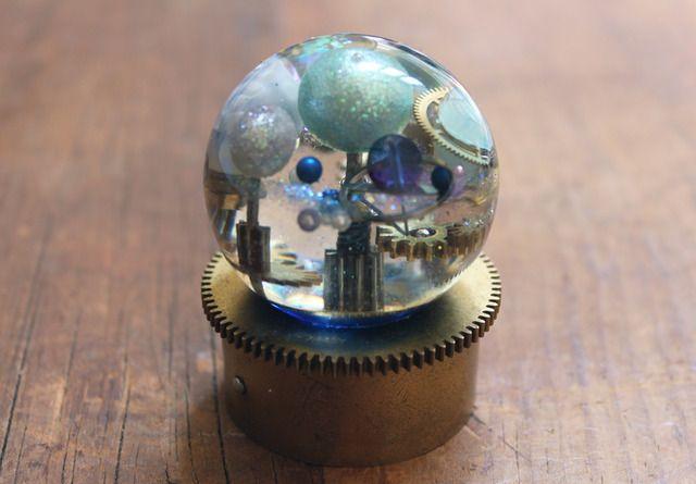 中心にある恒星の活動によって影響を受ける惑星への予報を視覚化したドーム。フレア現象、ガス状のプラズマによる風や磁場を乱れさせる磁気嵐などが観測でき、各惑星ごとに影響を予報する。使用部品  ヴィンテージの時計香箱車、針、歯車  ヴィンテージグラスビーズなどドーム直径約5cm、高さ約6.5cm