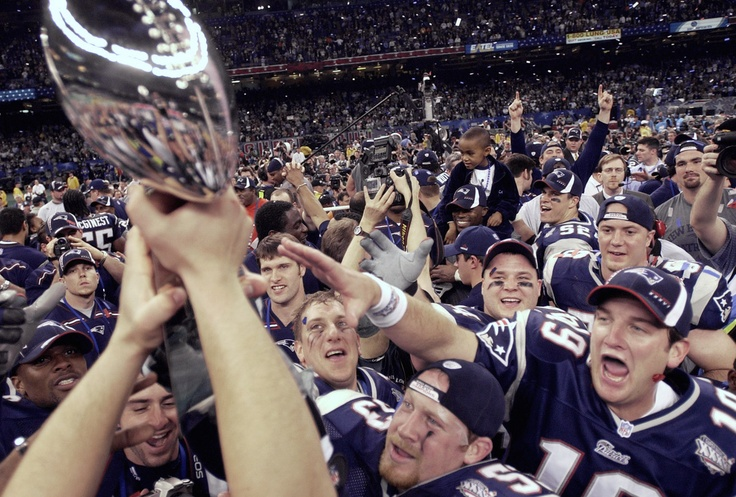 Super Bowl XXXVI -- New England Patriots 20, St. Louis Rams 17  FEB. 3, 2002 (Louisiana Superdome, New Orleans) -- New England Patriots players reach out to touch the Vince Lombardi Trophy after they beat the St. Louis Rams. (AP Photo/David J.
