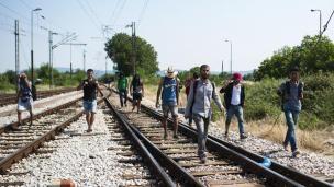 Sejumlah imigran berjalan menyusuri rel kereta api saat perjalanan menuju Gevgelija, wilayah perbatasan Macedonia-Yunani, Kamis (9/7/2015). Mereka menempuh ribuan kilometer agar dapat mengejar kereta api tujuan Serbia.