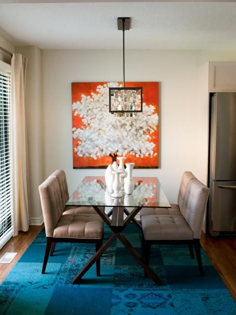 Jonathan and Drew wanted to get rid of the old mismatched sofa and make room for a formal dining area in the Horsman home. The reflective chandelier creates more brightness in the room and the pop of color in the painting draws in your eye.