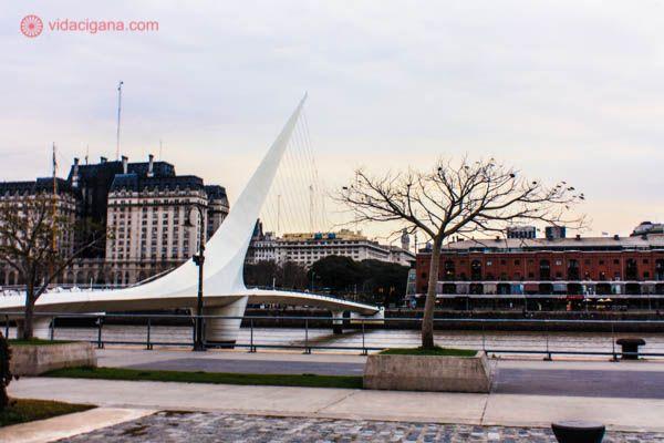 A Ponte de la Mujer em Puerto Madero, em Buenos Aires. A ponte está do lado esquerdo e possui uma forma bastante diferente. Ela é branca e estaiada, com vários cabos em sua extensão. Uma árvore está do lado direito da foto. O céu está nublado. Prédios aparecem ao fundo.