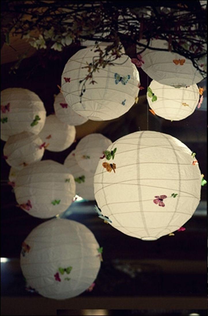 Nuée de papillons pastels posée sur des boules chinoises en papier
