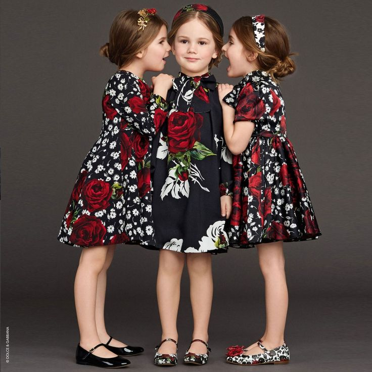 Girls stunning black crêpe dress byDolce & Gabbana featuring the designer's red rose print with contrasting large white roses, taken from the ladieswear collection. With a Spanish influence, it has balloon sleeves with a high neck and ready made bow.