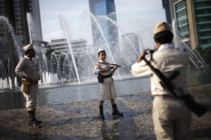 An Indonesian boy poses for photographs as he wears a costume resembling an Indonesian independence hero in Jakarta...