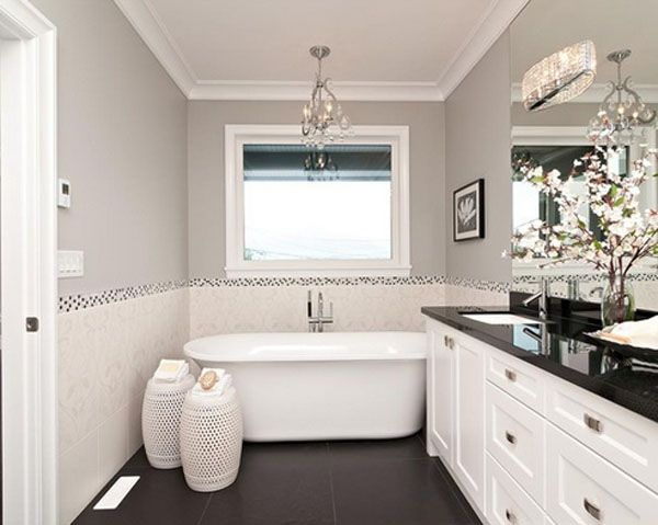 #Monochromatic #bathroom #design with matching white garden #stools, elegant #floral arrangement, and white #cabinets with a black #countertop.  Love this look!