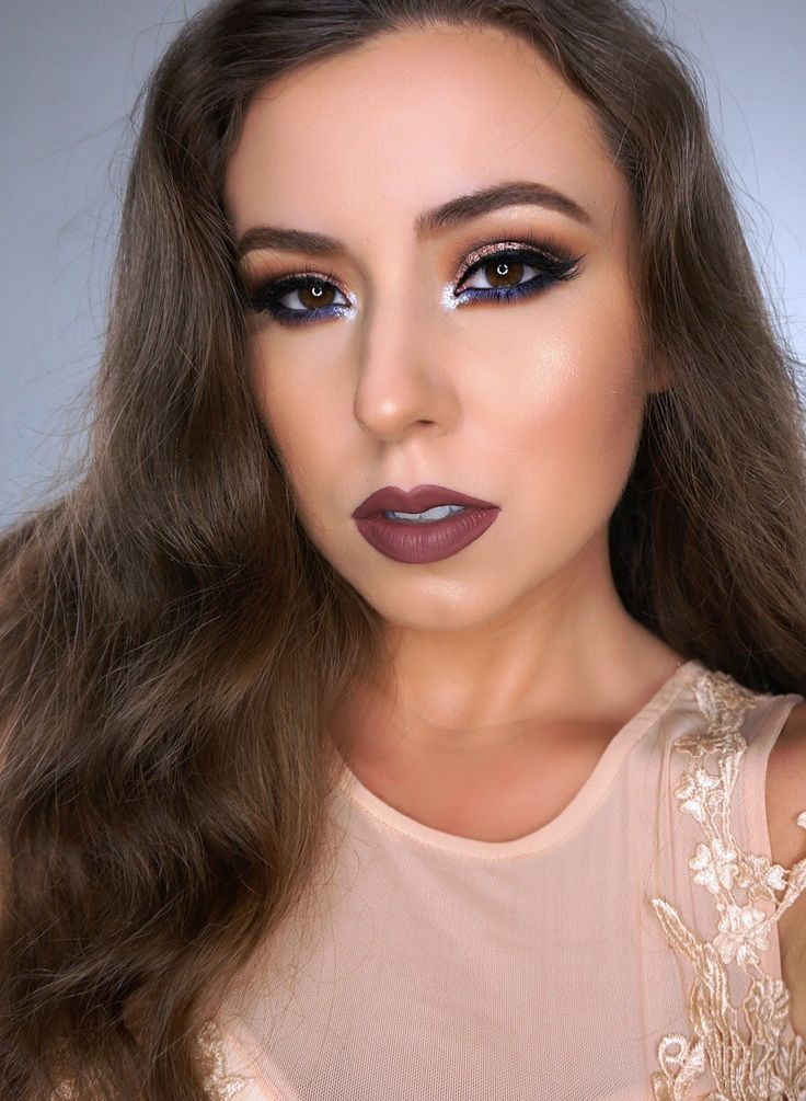 Deep colors like soft brown, burnt orange and black in crease the eyes. Finished with a deep mauve lipstick//