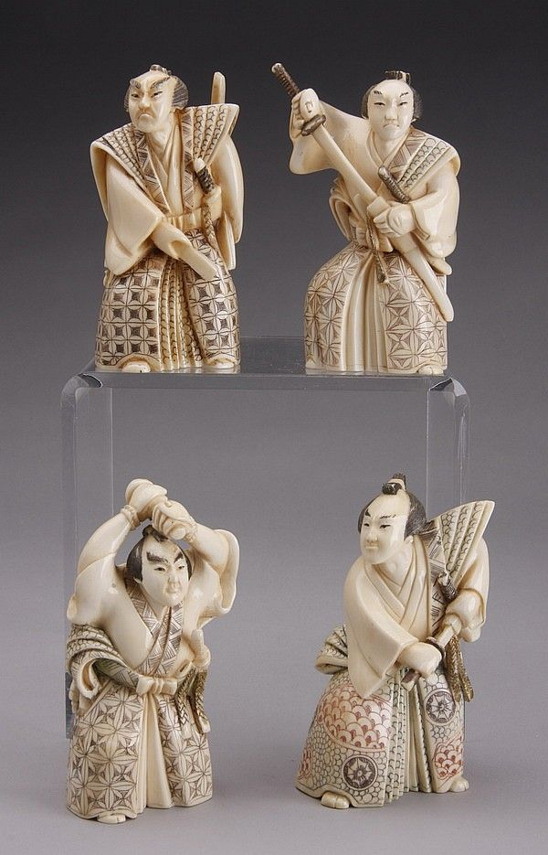 "Grouping of four carved ivory figurines of robed Japanese Samurai warriors wielding swords, each approximately 4""h x 2.5""w x 1.5""d."