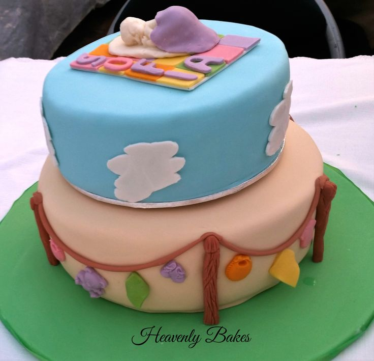 2 tier Christening Cake with clothes on the line and sleeping baby topper on a quilted blanket. Facebook://heavenlybakesaltona