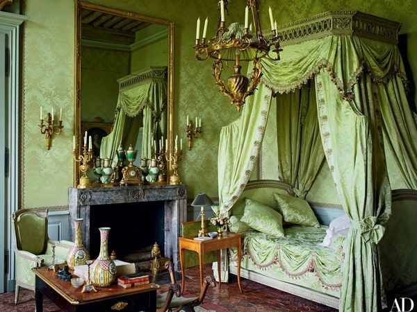 Château de Digoine, French Filmmaker Jean-Louis Remilleux's Antique-Filled Chateau... Anchoring another bedroom is a late-18th-century lit à la polonaise once owned by Madame Roland, a noted political activist during the French Revolution; Louis XV gilt-bronze sconces flank the mirror, and the antique bed side table features an integral screen for deflecting drafts or heat from the fireplace.