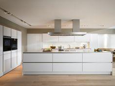 une cuisine en blanc avec une hotte aspirante moderne et un îlot