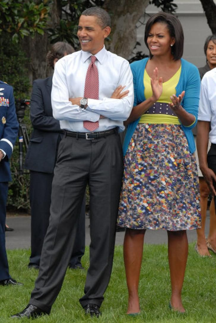 The First Lady keeps her look summery with a floral high-waisted skirt, yellow top, and blue cardigan as she and Barack cheer on Olympic fencers demonstrating their skills on the White House lawn on Sept. 16.